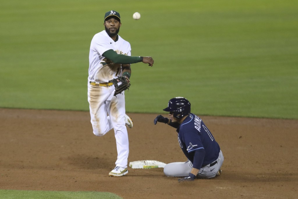 Oakland Athletics' Elvis Andrus throws to first as Tampa Bay Rays' Randy Arozarena slides into second on a ball hit by Yandy Diaz, who was safe during...