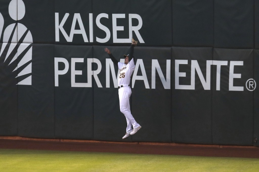 Oakland Athletics' Stephen Piscotty catches a fly ball hit by Tampa Bay Rays' Brandon Lowe during the seventh inning of a baseball game in Oakland, Ca...
