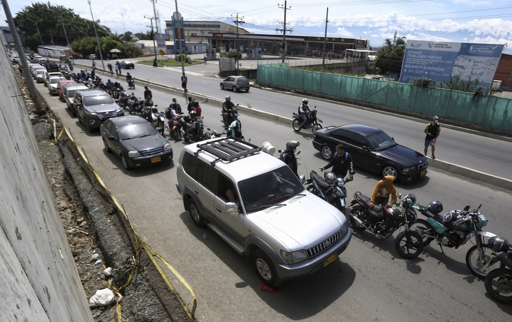 Drivers and motorcyclists wait their turn to fill up at a gas station in Cali, Colombia, Friday, May 7, 2021. Protesters are blocking the main roads a...