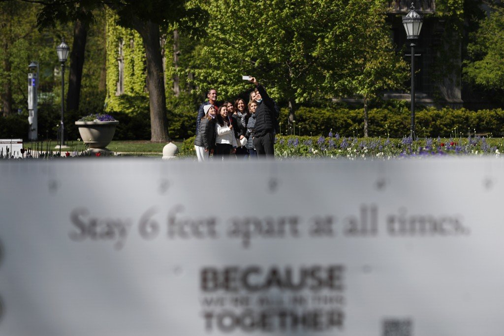 """A group of visitors take a selfie near a sign reading """"stay 6 feet apart at all times,"""" Thursday, May 6, 2021, on the University of Chicago campus in ..."""