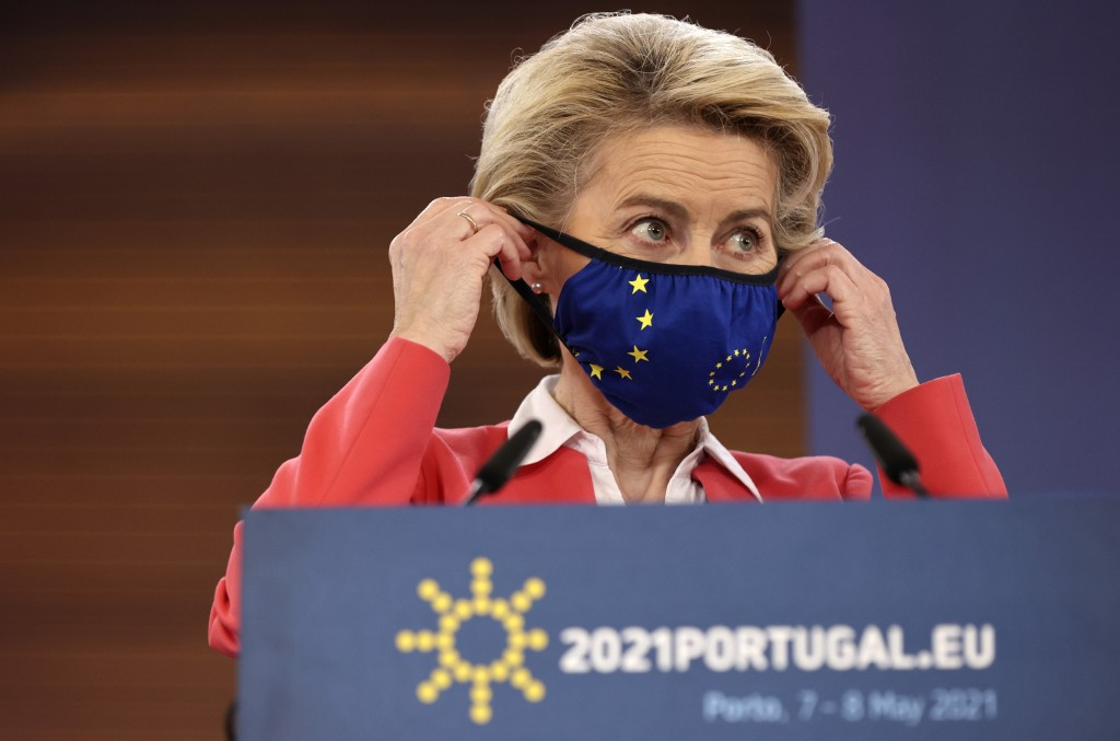 European Commission President Ursula von der Leyen puts on her protective face mask at the conclusion of a media conference at an EU summit in Porto, ...