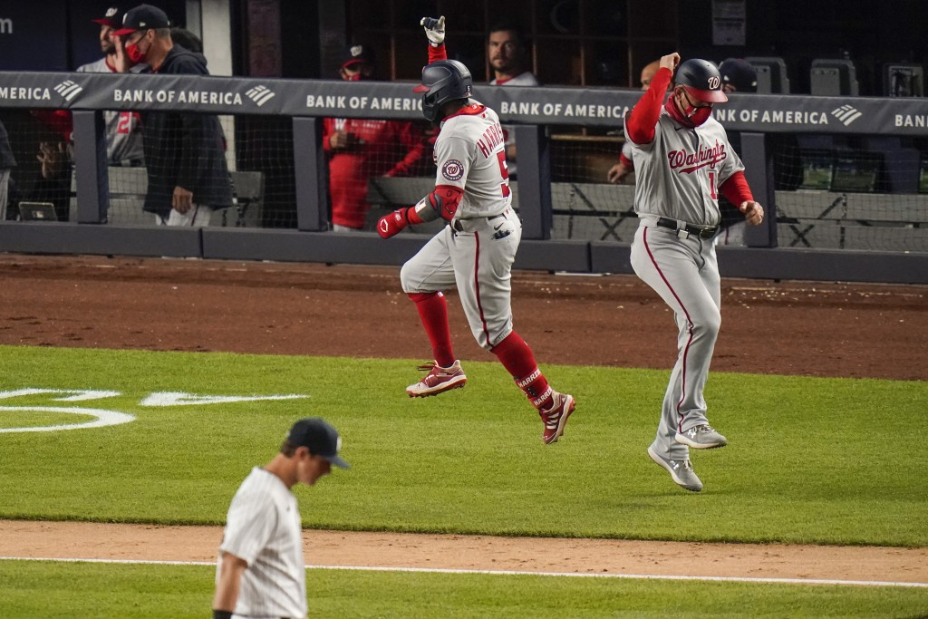 Washington Nationals' Josh Harrison (5) celebrates with third base coach Bob Henley after hitting a three-run home run during the eighth inning of the...