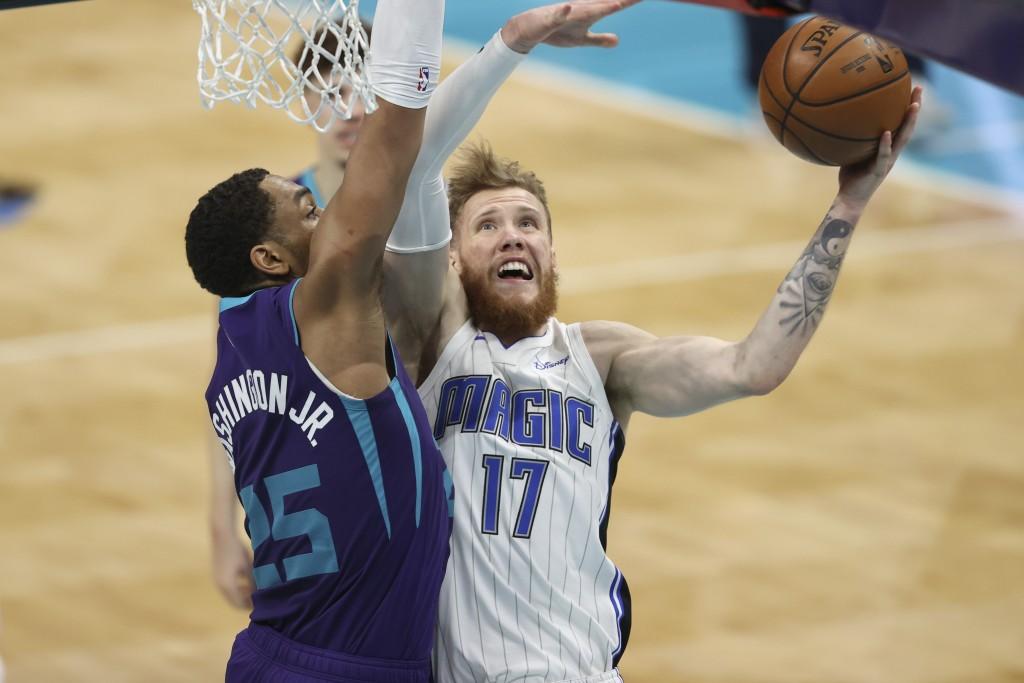 Orlando Magic forward Ignas Brazdeikis, right, shoots against Charlotte Hornets forward P.J. Washington during the second half of an NBA basketball ga...