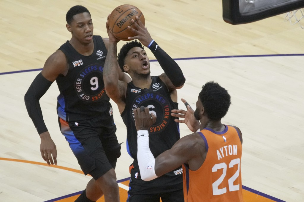 New York Knicks guard Elfrid Payton (6) shoots over Phoenix Suns center Deandre Ayton (22) during the first half of an NBA basketball game, Friday, Ma...