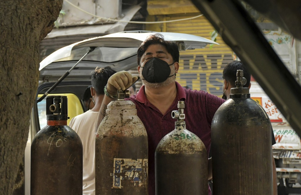 Family member of a COVID-19 patient reacts as he waits to refill an oxygen cylinder at a gas supplier facility in New Delhi, India, Saturday, May 8, 2...