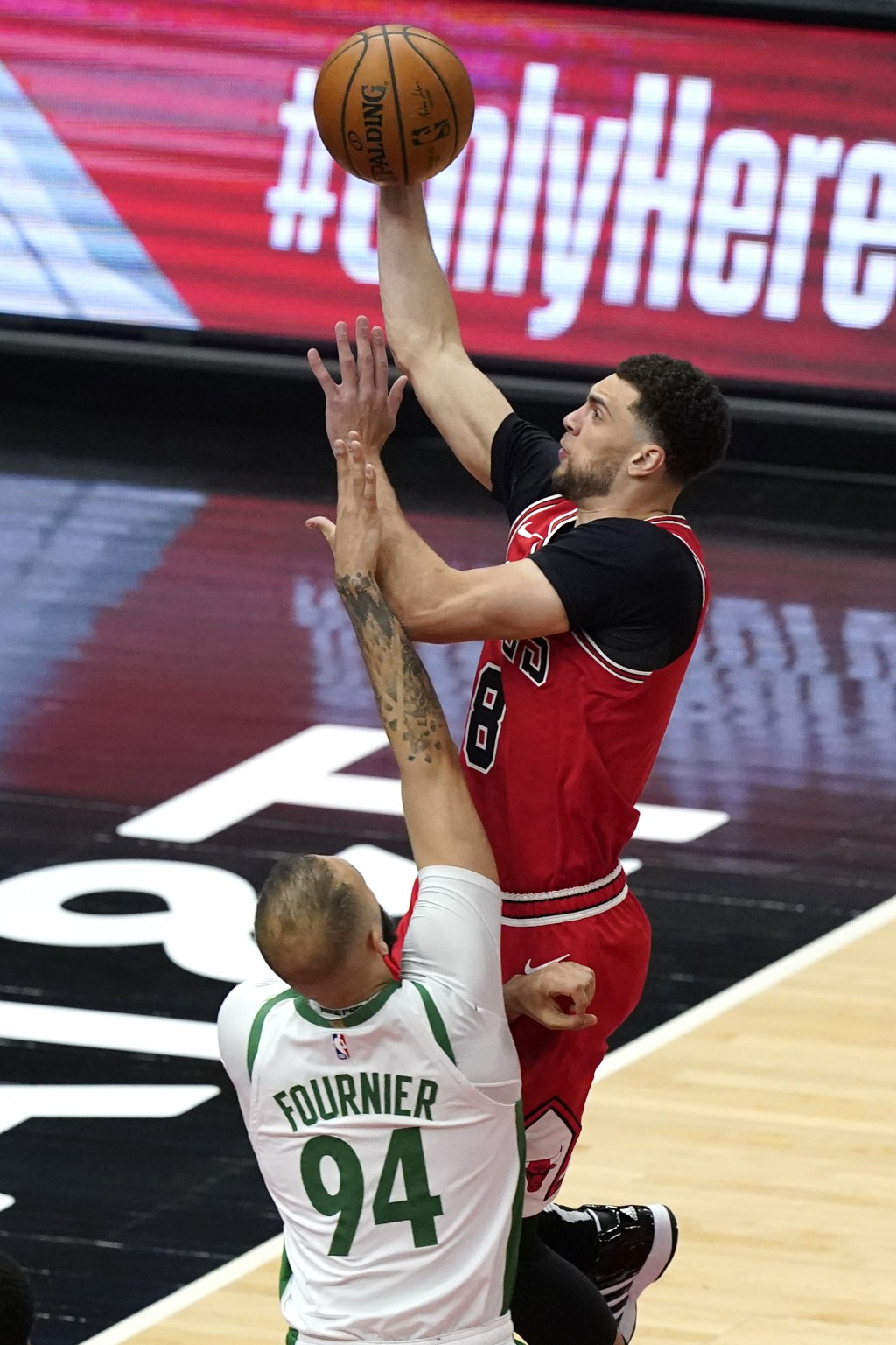 Chicago Bulls guard Zach LaVine, top, drives to the basket against Boston Celtics guard Evan Fournier during the first half of an NBA basketball game ...