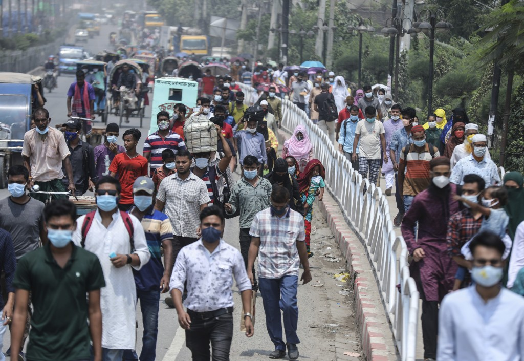 People wearing face masks a precaution against the coronavirus leave the city to travel to their native places ahead of Eid al-Fitr in Dhaka, Banglade...