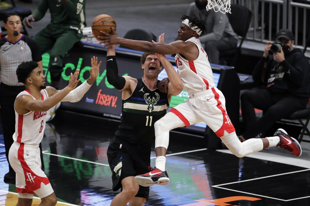 Milwaukee Bucks' Brook Lopez (11) is fouled by Houston Rockets' Danuel House Jr. during the first half of an NBA basketball game Friday, May 7, 2021, ...