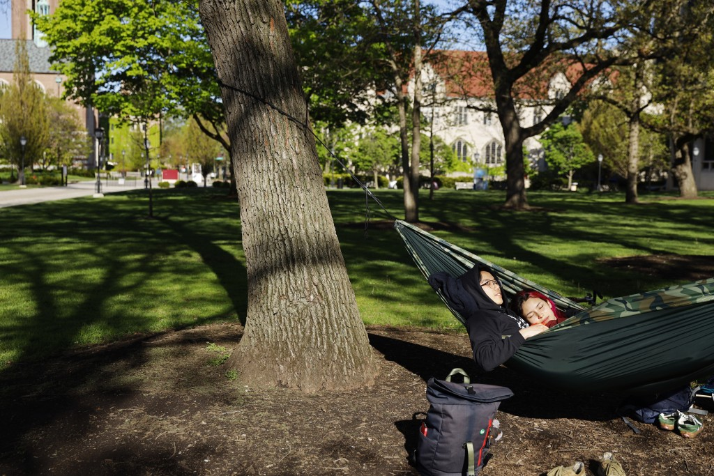 University of Chicago sophomore Silvana Montagu, right and Sonny Lee take advantage of warm spring weather as they spend time in a hummock Thursday, M...