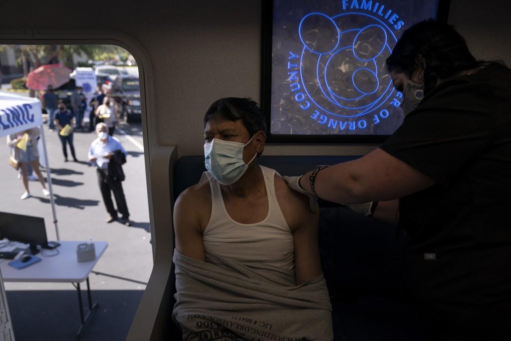 FILE - In this April 29, 2021, file photo, Nurse Natasha Garcia administers a dose of the Moderna COVID-19 vaccine to Samuel Sanchez in a mobile clini...