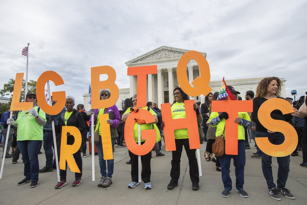 FILE - In this Oct. 8, 2019, file photo, supporters of LGBTQ rights hold placards in front of the U.S. Supreme Court, on Capitol Hill in Washington. L...