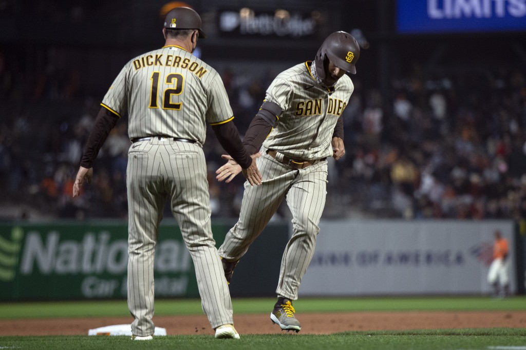 San Diego Padres' Trent Grisham, right, gets a congratulatory handshake from third base coach Bobby Dickerson (12) after hitting a two-run home run ag...
