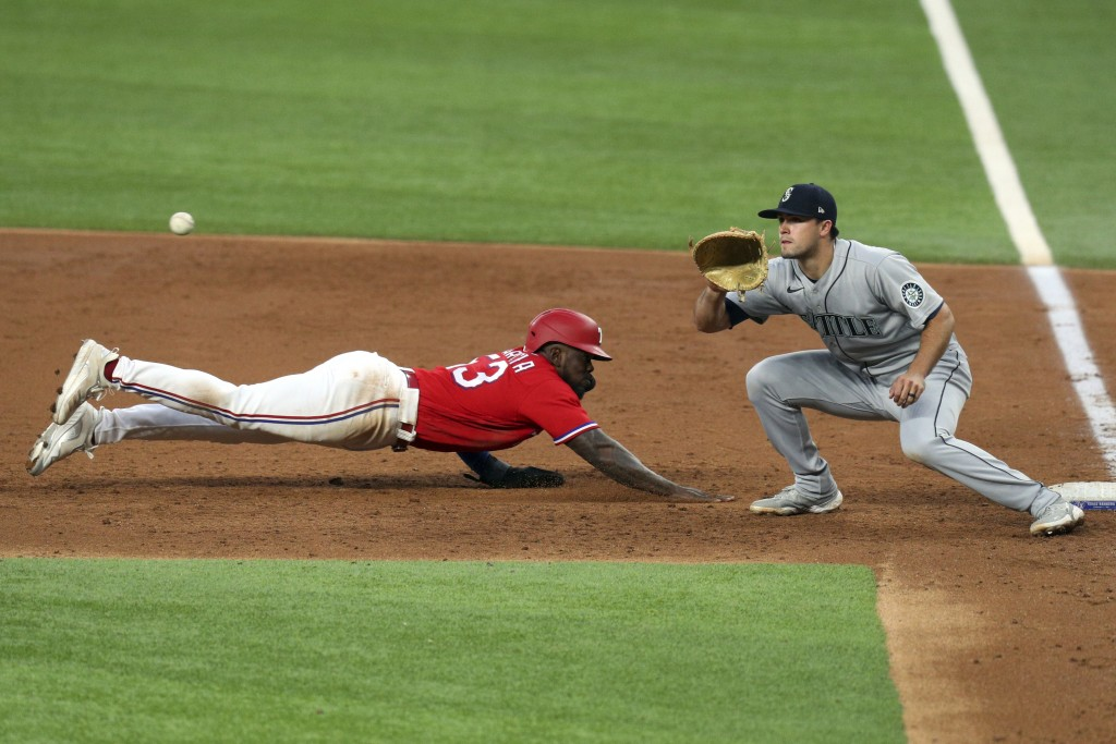 Texas Rangers' Adolis Garcia (53) dives back to first as Seattle Mariners first baseman Evan White (12) gets the pickoff throw during the third inning...