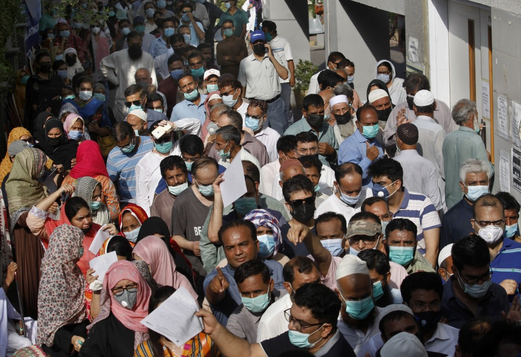 People stand in queues while they wait their turn to receive the first shot of the Sinopharm COVID-19 vaccine at a vaccination center in Karachi, Paki...
