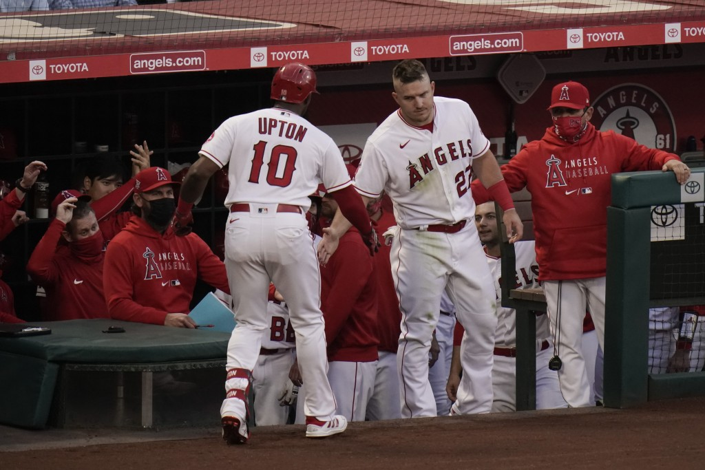 Los Angeles Angels' Justin Upton, left, is congratulated by Mike Trout after hitting a home run during the second inning of a baseball game against th...