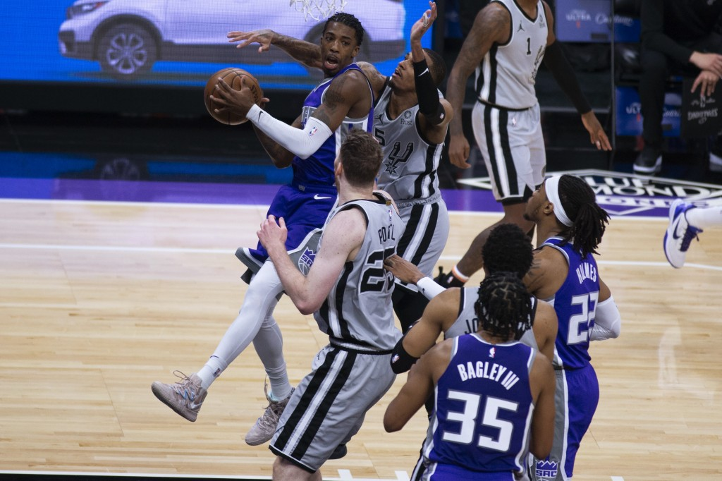 Sacramento Kings guard Delon Wright looks to make a pass as he's defended under the basket by San Antonio Spurs center Jakob Poeltl (25) during the fi...