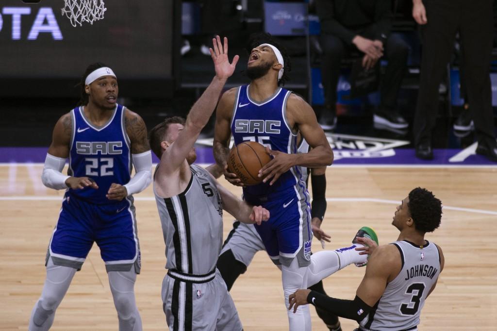 Sacramento Kings forward Marvin Bagley III (35) is fouled on his way to the basket by San Antonio Spurs forward Keldon Johnson (3) as Spurs center Jak...