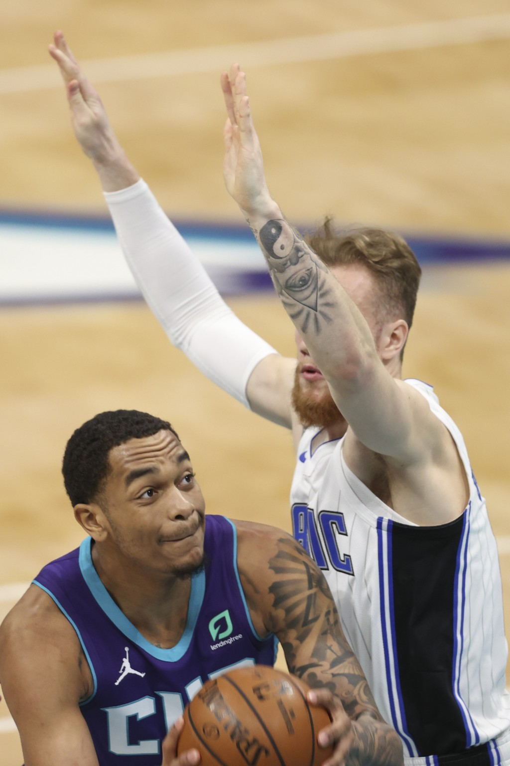 Charlotte Hornets forward P.J. Washington, left, is defended by Orlando Magic forward Ignas Brazdeikis during the first half of an NBA basketball game...