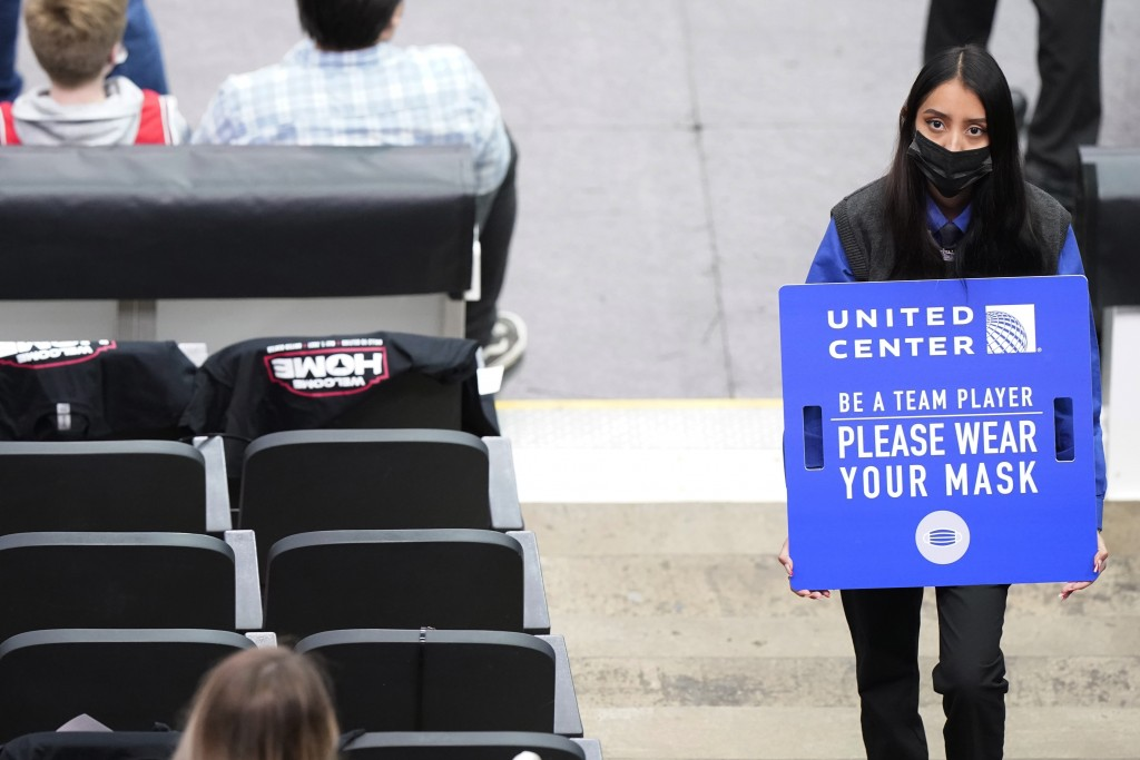 An usher holds a sign reminding fans about COVID-19 precautions, during the first half of an NBA basketball game between the Boston Celtics and the Ch...