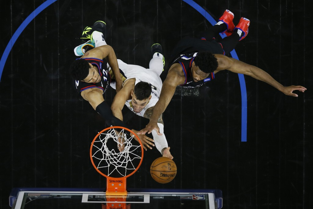 New Orleans Pelicans' Willy Hernangomez, center, goes up for a shot between Philadelphia 76ers' Tobias Harris, left, and Joel Embiid during the second...
