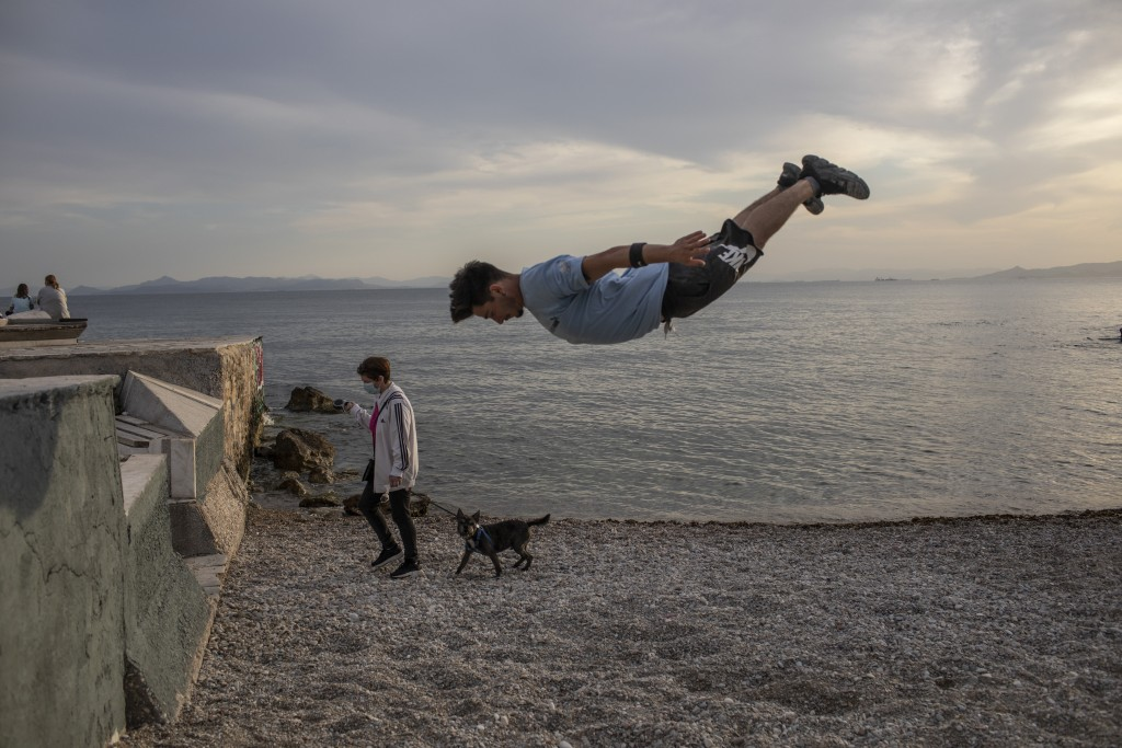 25 year-old Jimmakos Scotis makes a backflip as a woman wearing a protective face mask walks with her dog at the seaside of Alimos, suburb of Athens, ...