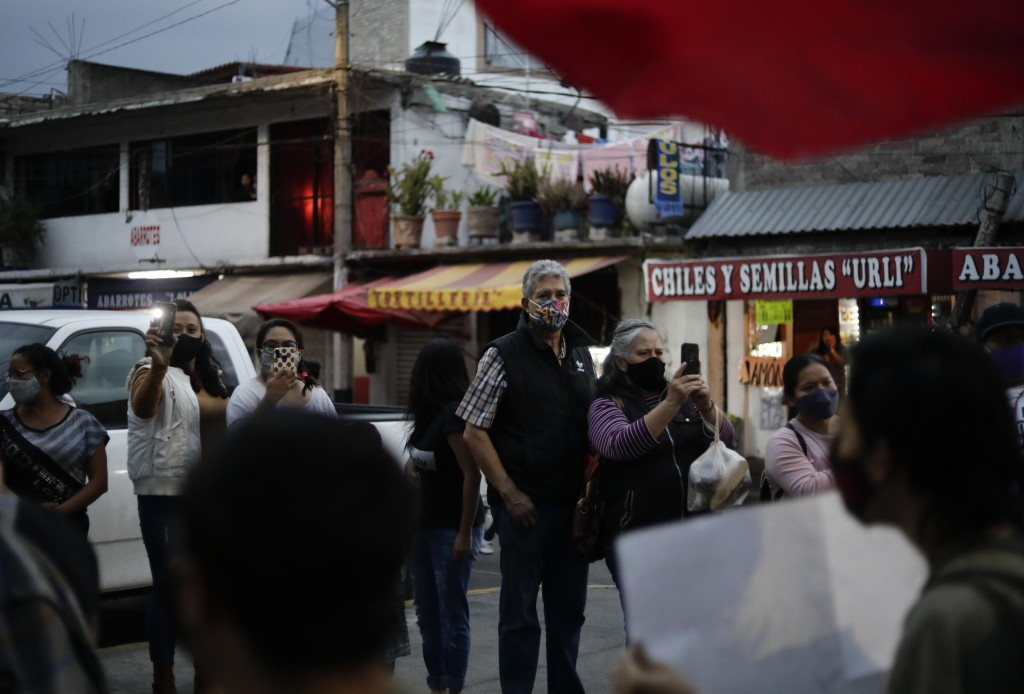 Residents watch a march demanding justice for the people who died in Monday's subway collapse, in Mexico City's south side, Friday, May 7, 2021. An el...