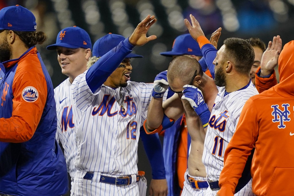 New York Mets' Francisco Lindor (12) celebrates with Patrick Mazeika, center right, who had his jersey removed by his teammates as they celebrate afte...