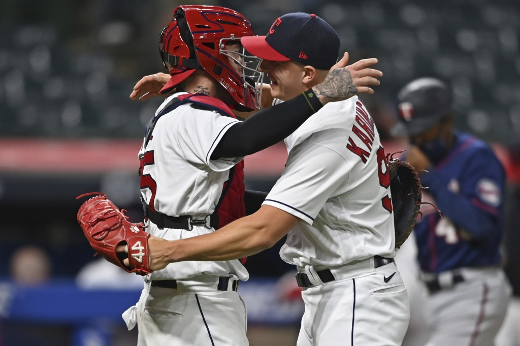 Cleveland Indians' relief pitcher James Karinchak (99) is congratulated by catcher Roberto Perez after the Indians defeated the Minnesota Twins in a b...