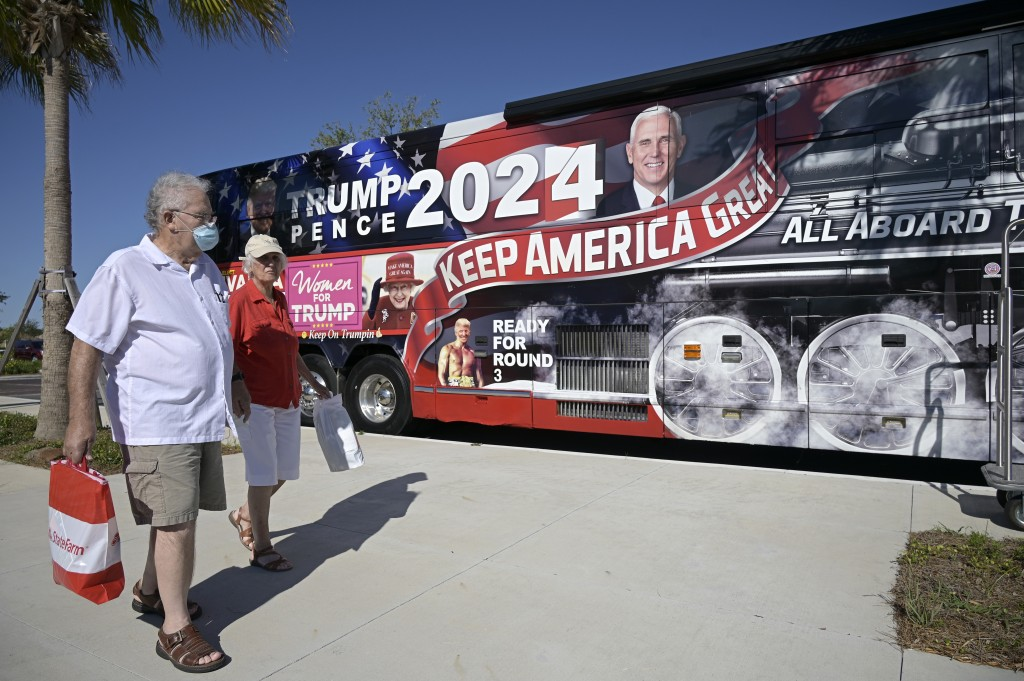People walk past a bus wrapped with President Donald Trump photos during a Gaetz/Greene rally, Friday, May 7, 2021, in The Villages, Fla. (AP Photo/Ph...