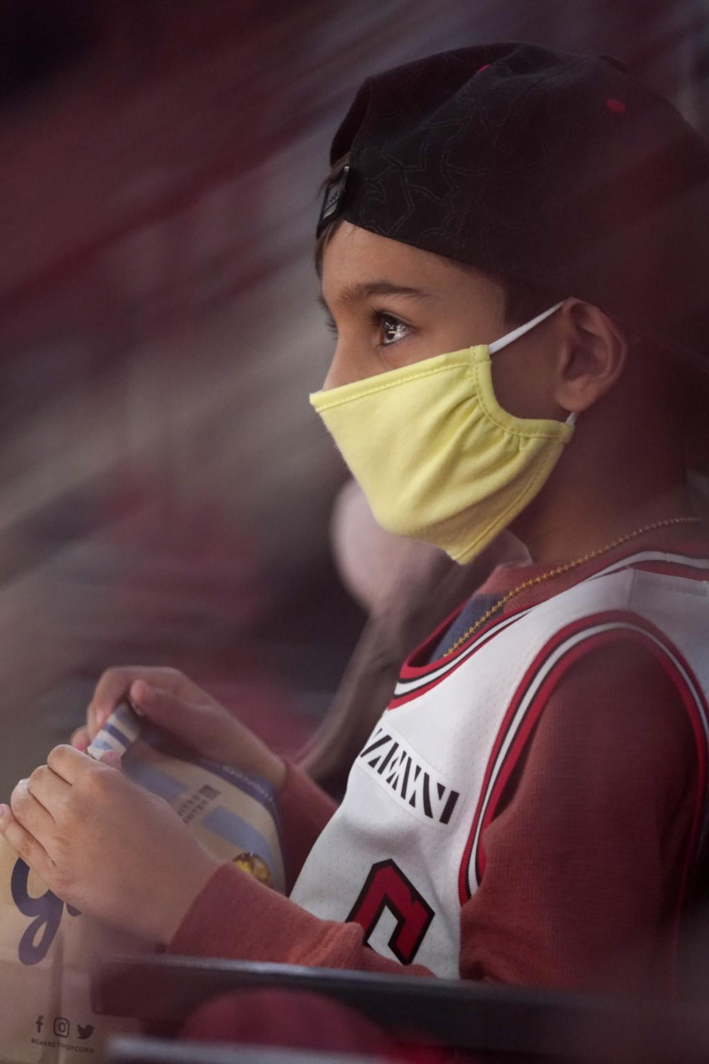 Jaxen Desai, 7, wears mask as he watches the first half of an NBA basketball game between the Boston Celtics and the Chicago Bulls in Chicago, Friday,...
