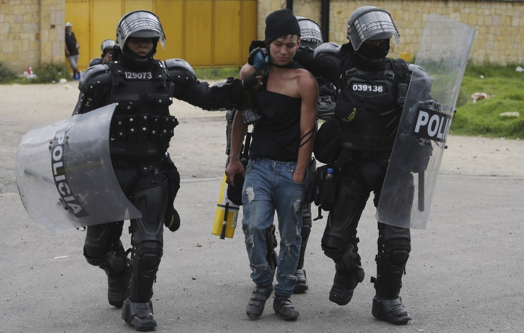 An anti-government protester is detained by police in Gachancipa, Colombia, Friday, May 7, 2021. The protests that began last week over a tax reform p...
