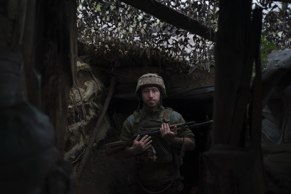 A Ukrainian poses for a photo at a fighting position on the line of separation from pro-Russian rebels near Toretsk, eastern Ukraine, Thursday, May 6,...