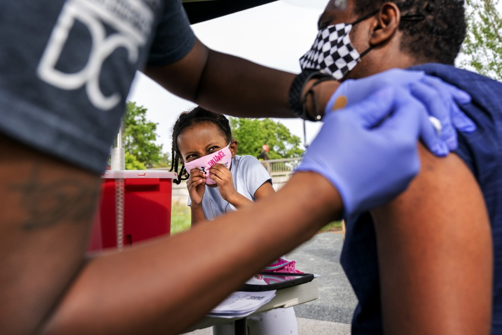 Heran Abebe, 6, reacts as she watches her father Alebel Belay receive a Johnson & Johnson COVID-19 vaccine shot, Thursday, May 6, 2021, at The REACH a...