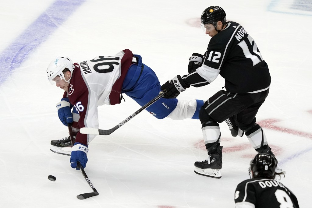Colorado Avalanche right wing Mikko Rantanen, left, reaches for the puck in front of Los Angeles Kings center Trevor Moore (12) during the second peri...