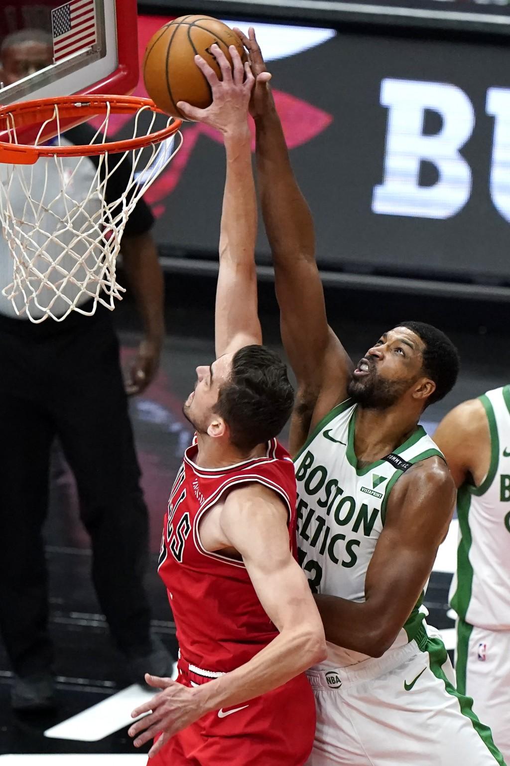 Boston Celtics center Tristan Thompson, right, blocks a shot by Chicago Bulls guard Tomas Satoransky during the first half of an NBA basketball game i...