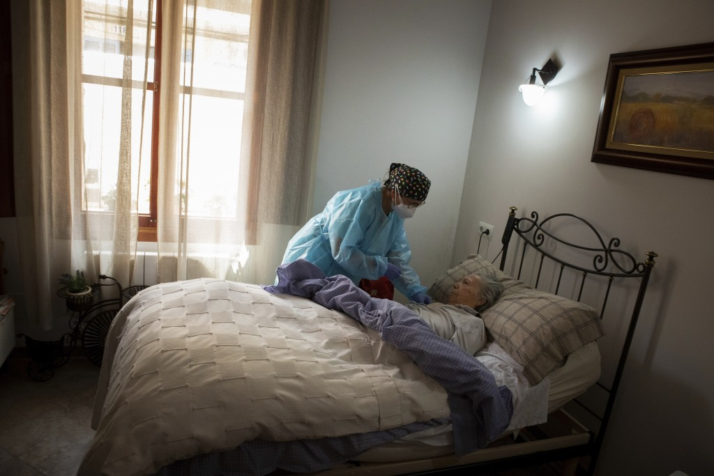 Nurse Pilar Rodríguez administers the COVID-19 vaccine to her patient Margarita Serra Crespi, 93, at her home in the town of Sa Pobla on the Spanish B...