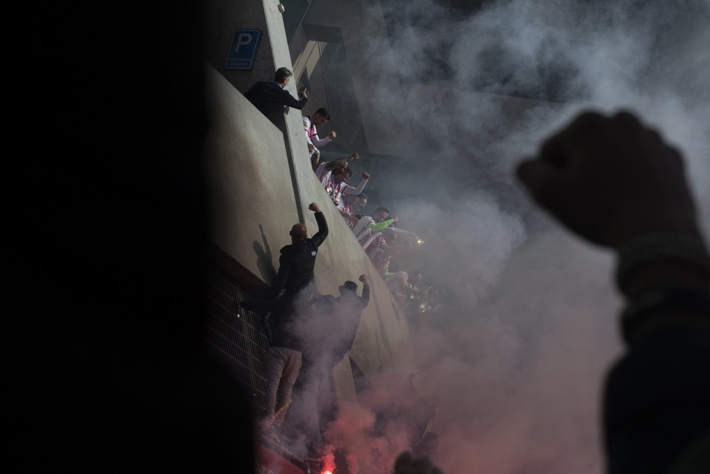 Supporters cheer as Ajax players, center, show the trophy after clinching the Dutch Eredivisie Premier League title with a 4-0 win in the soccer match...