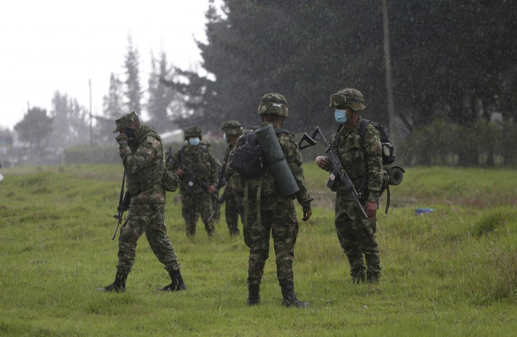 Colombian soldiers stand guard near a highway while anti-government protesters clash with police, in Gachancipa, Colombia, Friday, May 7, 2021. The pr...