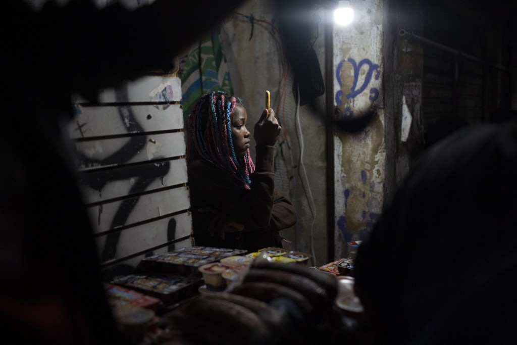 A girl takes photos of a protest a day after a deadly police operation in the Jacarezinho favela of Rio de Janeiro, Brazil, Friday, May 7, 2021. A blo...