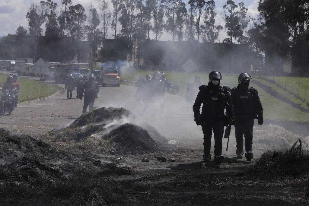 Police walk along highway as they work to unblock it from anti-government protesters so trucks can pass, in Gachancipa, Colombia, Friday, May 7, 2021....