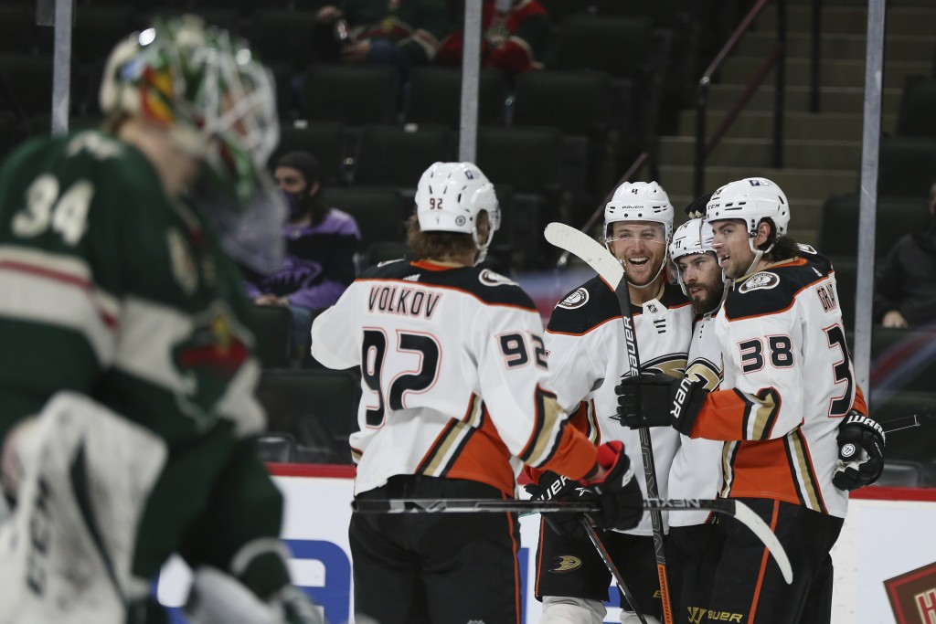 Anaheim Ducks' Adam Henrique (14) is surrounded by teammates after scoring a goal against the Minnesota Wild during the second period of an NHL hockey...