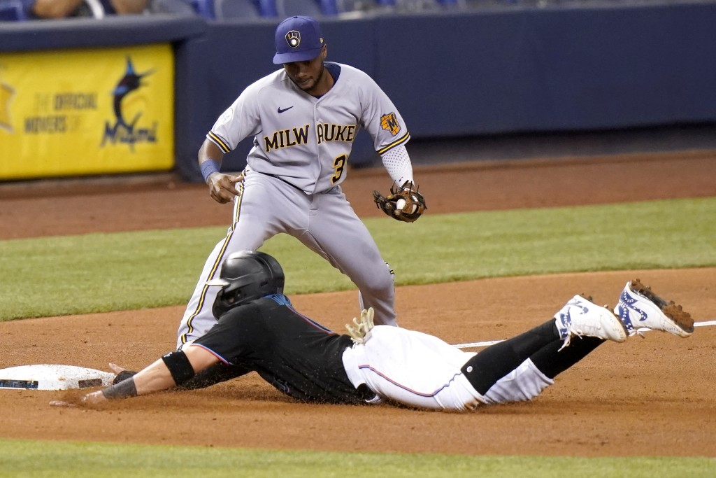 Miami Marlins' Miguel Rojas, bottom, slides past Milwaukee Brewers third baseman Pablo Reyes (33) as he is safe on a single hit by Garrett Cooper duri...