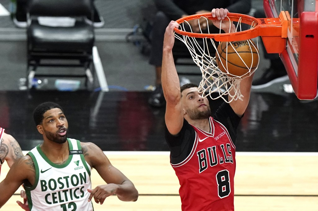 Chicago Bulls guard Zach LaVine, right, dunks past Boston Celtics center Tristan Thompson during the second half of an NBA basketball game in Chicago,...