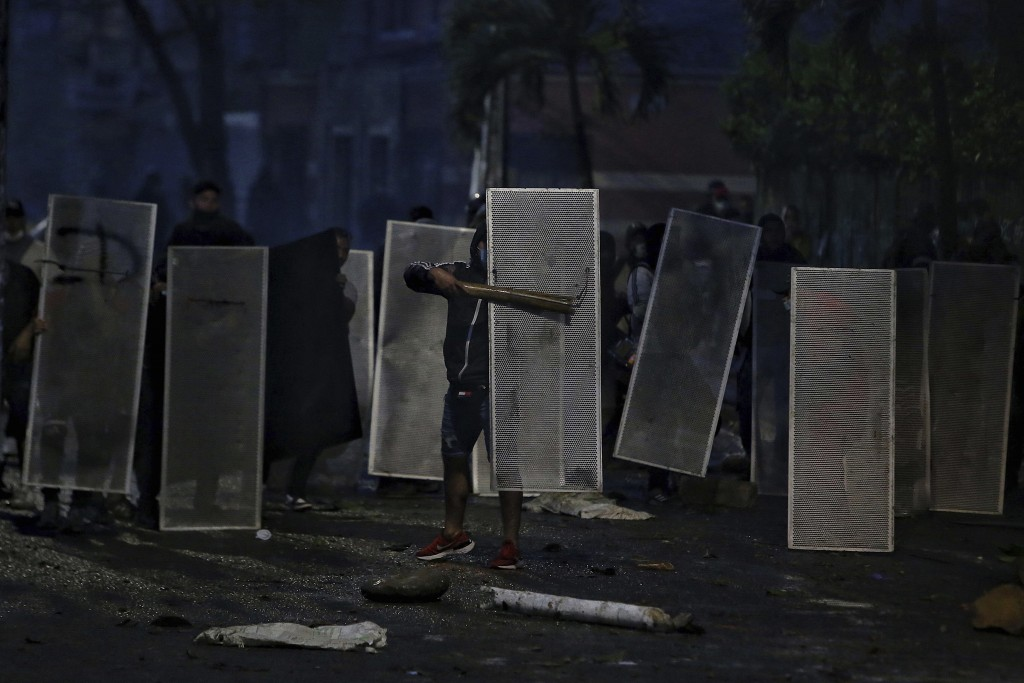 Protesters protect themselves with makeshift shields in clashes with police during a national strike to protest government-proposed tax reform, in Cal...