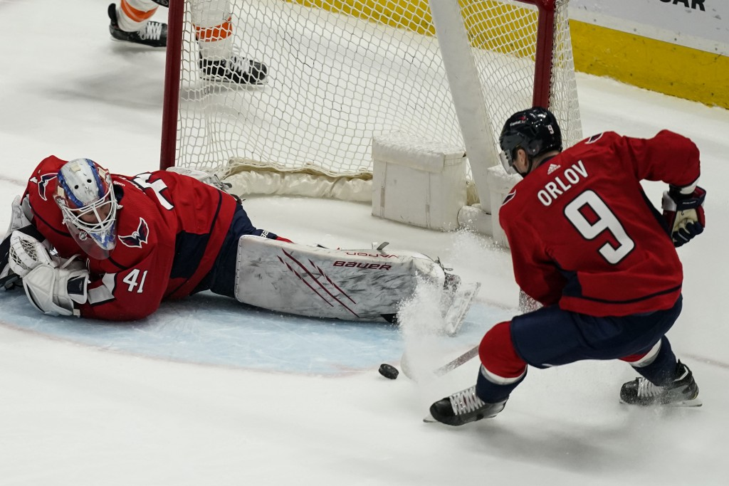 Washington Capitals defenseman Dmitry Orlov (9) clears the puck from in front of goaltender Vitek Vanecek (41) during the first period of an NHL hocke...