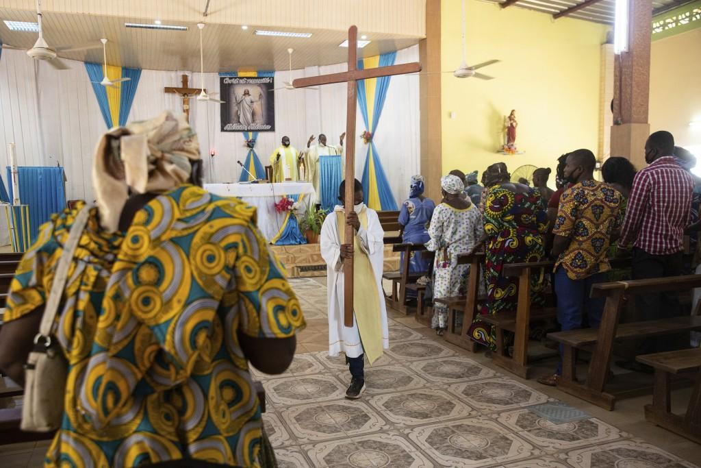 An altar boy carries a cross as Noel Henri Zongo, priest at the Church of the Sangoulé Lamizana military camp in Ouagadougou, Burkina Faso, celebrates...