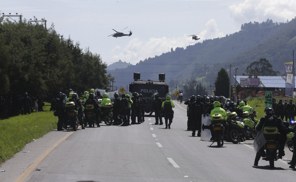 Police stand on a highway during anti-government protests and roadblocks in Gachancipa, Colombia, Friday, May 7, 2021. Protests that began last week o...