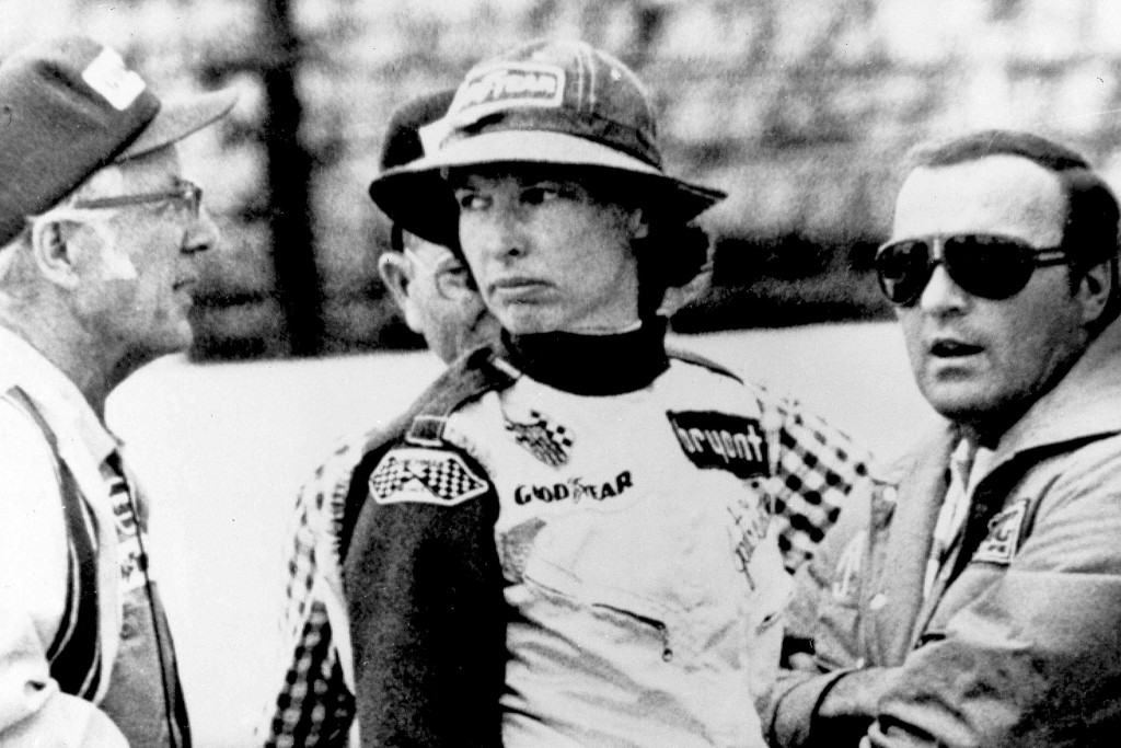 FILE - In this May 23, 1976, file photo, Janet Guthrie talks to racing car owner-builder Rolla Vollstedt, left, and A.J. Foyt, right, in the pits of t...