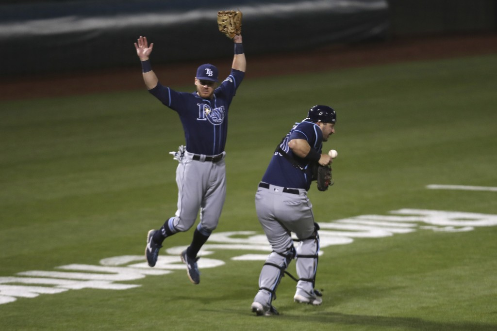 Tampa Bay Rays' Mike Zunino, right, misses a foul ball hit by Oakland Athletics' Tony Kemp as Mike Brosseau avoids the play during the seventh inning ...