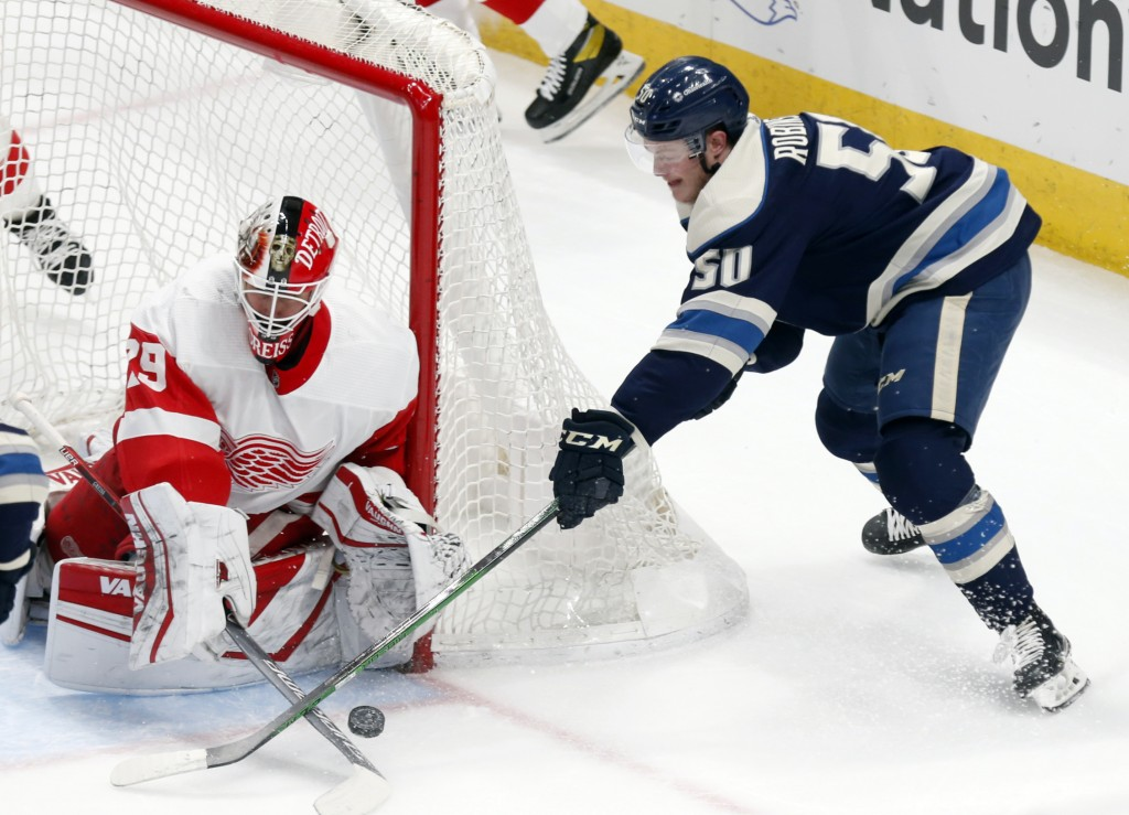 Detroit Red Wings goalie Thomas Greiss, left, stops a shot by Columbus Blue Jackets forward Eric Robinson during the first period of an NHL hockey gam...